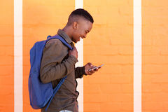 Smiling black guy walking with bag and mobile phone. Profile portrait of smiling black guy walking with bag and mobile phone Royalty Free Stock Photo