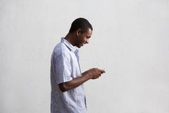 Smiling black guy walking and using mobile phone Stock Image