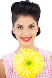 Smiling black hair woman showing a flower Royalty Free Stock Image