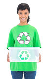 Smiling black haired ecologist holding a recycling box Stock Photography