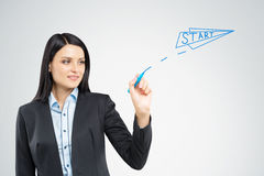 Smiling black haired woman is drawing start paper plane in the a Stock Photography