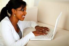 Smiling black lady working on laptop Stock Photo