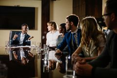 Black male boss talking to business team in conference room. Smiling black male boss talking to business team in conference room Royalty Free Stock Photos