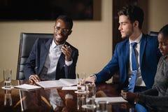 Black male boss talking to business team in conference room. Smiling black male boss talking to business team in conference room Stock Photo