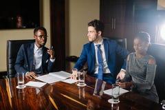Black male boss talking to business team in conference room. Smiling black male boss talking to business team in conference room Stock Image