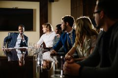 Black male boss talking to business team in conference room. Smiling black male boss talking to business team in conference room Royalty Free Stock Images
