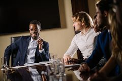 Black male boss talking to business team in conference room. Smiling black male boss talking to business team in conference room Royalty Free Stock Image