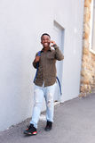 Smiling black male student walking and talking on mobile phone. Full length portrait of smiling black male student walking and talking on mobile phone Stock Photography