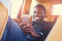 Black male using a smart phone in a car. Smiling Black male using a smart phone in a car Royalty Free Stock Image