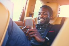 Black male using a smart phone in a car. Smiling Black male using a smart phone in a car Royalty Free Stock Photography