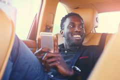 Black male using a smart phone in a car. Smiling Black male using a smart phone in a car Royalty Free Stock Images