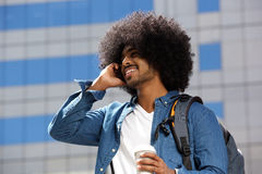 Smiling black man with afro using mobile phone in the city Stock Photos