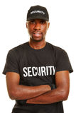 Smiling black man as security guard. With his arms crossed Stock Image