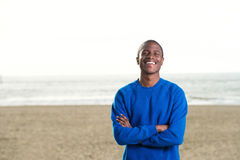 Smiling black man in blue sweatshirt at the beach Stock Photography