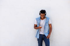 Smiling black man leaning against wall with smart phone and headphones stock photo
