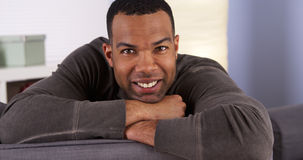 Smiling black man resting on couch smiling Royalty Free Stock Photo