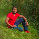Smiling black man resting in the park. Royalty Free Stock Image
