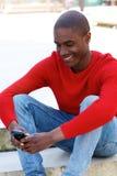 Smiling black man sitting outside using cellphone. Portrait of smiling black man sitting outside using cellphone Stock Image
