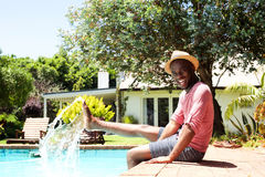 Smiling black man sitting by pool Royalty Free Stock Photos