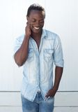 Smiling black man standing outdoors against white background Stock Photos