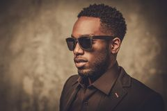 Smiling black man with sunglasses posing on dark background. Royalty Free Stock Images