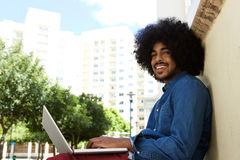 Smiling black man using laptop in the city Royalty Free Stock Photography