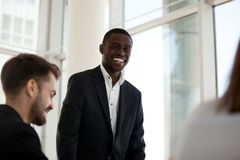 Smiling black mentor stand talking with employees during meeting. Smiling African American male standing talking during office meeting, happy confident black royalty free stock photography