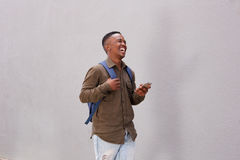 Smiling black student walking with cellphone and bag. Portrait of smiling black student walking with cellphone and bag Royalty Free Stock Image