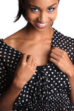 Smiling black teenage girl. Close up portrait of smiling black teenage girl in spotted dress, isolated on white background royalty free stock photography