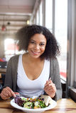 Smiling black woman eating salad at restaurant. Portrait of a smiling black woman eating salad at restaurant Royalty Free Stock Photos