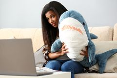 Smiling black woman hold in hands shark toy royalty free stock photography