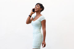 Smiling black woman listening to mobile phone Royalty Free Stock Photo