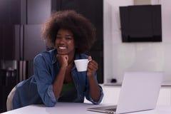 Smiling black woman in modern kitchen Stock Photos