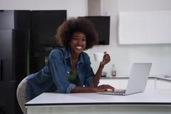 Smiling black woman in modern kitchen Stock Image
