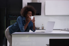 Smiling black woman in modern kitchen Stock Photography