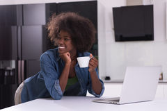 Smiling black woman in modern kitchen Stock Images