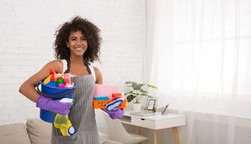 Smiling black woman posing with cleaning supplies. Smiling african-american woman posing with cleaning supplies, housewife preparing detergents for housecleaning stock image