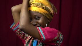 Smiling black woman in scars posing in traditional clothes, slow motion. A nice black woman in African traditional clothes posing in the studio, slow motion stock footage