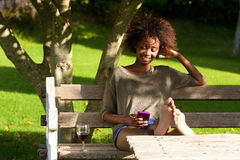 Smiling black woman sitting in park with mobile phone Stock Photos