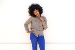 Smiling black woman standing with hand to shirt collar. Portrait of smiling black woman standing with hand to shirt collar royalty free stock photos