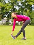 Smiling black woman stretching leg outdoors Royalty Free Stock Photos
