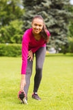 Smiling black woman stretching leg outdoors Stock Image
