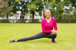 Smiling black woman stretching leg outdoors Stock Photography
