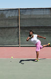 Smiling black woman swinging tennis Stock Photo