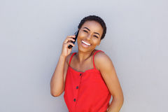 Smiling black woman talking on cellphone against gray wall Royalty Free Stock Photography