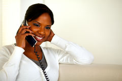 Smiling black woman talking on phone at home Royalty Free Stock Photo