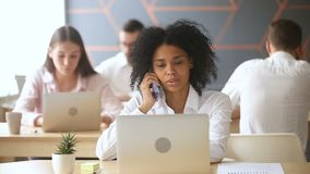 Smiling black woman using laptop, talking on phone at workplace. Smiling black woman using laptop talking on the phone at workplace, nice polite african manager