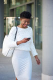 Smiling black woman walking outside with mobile phone Stock Photography
