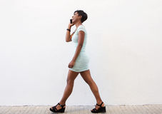 Smiling black woman walking on street with cell phone Royalty Free Stock Images