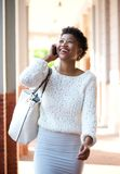 Smiling black woman walking and talking with cell phone Royalty Free Stock Image